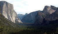 "El Capitan, left, Half Dome, center, and Bridalveil Falls are seen in this view from near the tunnel on WInona Highway in one of the most famous views of Yosemite Valley in California on November 24, 2008. Yosemite's Tunnel View Overlook, located next to Wawona Road at the east portal of the Wawona Tunnel, was constructed during an era that heralded a boom in design and development throughout the National Park Service, and helped initiate the service's ""rustic"" design style. Because of their exemplary park service rustic design, Wawona Tunnel and Tunnel View are listed on the National Register of Historic Places. The site remains one of the most popular scenic overlooks in Yosemite National Park. Tour buses, tram tours, and single-family vehicles bring as many as 7,000 people to the site each day during the height of the visitor season. (Photo copyright Alan Greth)"