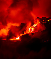 A slow red river of lava flows into the ocean at night near Hawai'i Volcanoes National Park and the Kalapana border, Big Island.