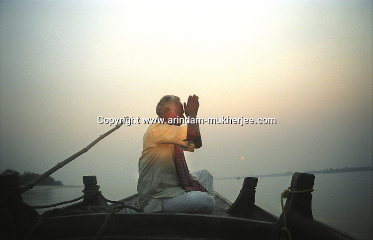 A boatman praying on his boat after coming out of the forest.  Sunderban, West Bangal, India. Dec 2005. Arindam Mukherjee