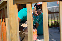 """Christian Sims applies wood stain to a gazebo during """"Circle the City with Service,"""" the Kiwanis Circle K International's 2015 Large Scale Service Project, on Wednesday, June 24, 2015, in Indianapolis. (Photo by James Brosher)"""