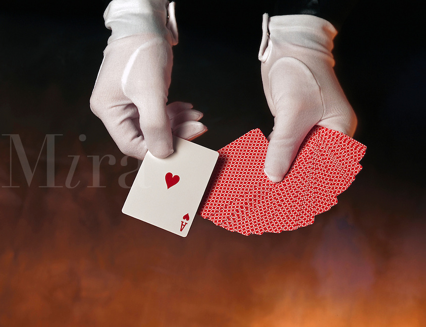 Magicians hands with deck of cards.