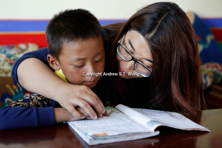 Lhasa, Tibet, China - Tibetan educator Deqingyuzhen teaches a young student to read during free classes at a community centre in Lhasa, September 2018.