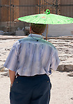 tourist with green umbrella to fight the sun in Greece at the Parthenon, at the Acropolis in Athens.  You can't stage these.