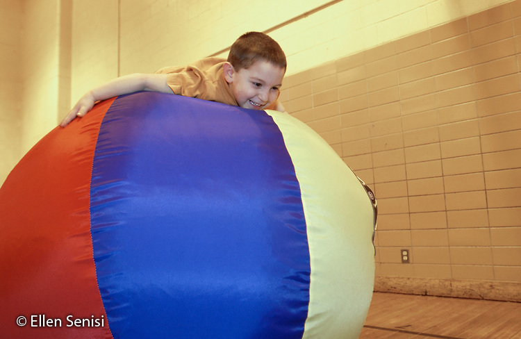 MR / Schenectady, NY                                  .Yates Arts-in-Education Magnet School (urban school).Pre-Kindergarten class; NYS Universal Pre-K Program.Boy (4) balances self and holds on to big ball on mat in gym class after being placed there by gym teacher..Rus1.©Ellen B. Senisi