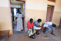 N. Uganda, Gulu District. Peter C. Alderman Foundation project. Initial psychiatric evaluations at Gulu Mental Hospital. As Dominic is being assessed another man is brought in with his hands tied behind his back He is so violent he has to be restrained and Susan Ayot , the PCAF nurse jumps in to help and assess. The man's wife and brother are weeping and visibly distraught.