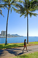 A woman walks the curving path through Aina Moana Park near Waikiki.  Diamond Head is in the background.