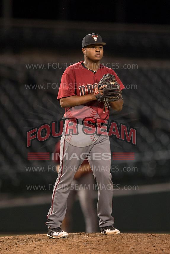 AZL Diamondbacks relief pitcher Ezequiel De La Cruz (14) checks a runner at first base during an Arizona League game against the AZL Cubs 1 at Sloan Park on June 18, 2018 in Mesa, Arizona. AZL Diamondbacks defeated AZL Cubs 1 7-0. (Zachary Lucy/Four Seam Images)