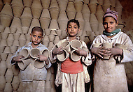 In Egypt, these children work in a pottery, producing plates, bowls, and pots. Child labor as seen around the world between 1979 and 1980 - Photographer Jean Pierre Laffont, touched by the suffering of child workers, chronicled their plight in 12 countries over the course of one year.  Laffont was awarded The World Press Award and Madeline Ross Award among many others for his work.