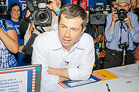 Media surround South Bend mayor and Democratic presidential candidate Pete Buttigieg as he greets people from the Democratic Party booth in the Varied Industries building at the Iowa State Fair in Des Moines, Iowa, on Tues., Aug. 13, 2019.
