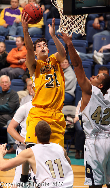 SIOUX FALLS, SD - NOVEMBER 28:  Cody Schilling #21 of Augustana lays in two points over Andrew Kuderer #11 and Thomas Bassett #42 of Concordia in the first half of their NSIC Holiday Hoopfest game Saturday night at the Sioux Falls Arena. (Photo by Dave Eggen/Inertia)