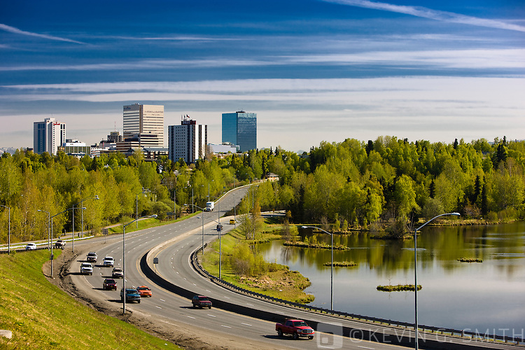 Commuter traffic passes by Westchester lagoon on the way to and from downtown Anchorage, spring foliage, Minnesota blvd. Anchorage, Southcentral Alaska, USA.