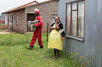 An evicted resident waits outside her hut as a member of the Red Ants removes her pots and pans in Evaton. <br />The Red Ants are a controversial private security company often hired to clear squatters from land and so-called 'hijacked' properties.