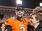 Oklahoma State Cowboys quarterback Brandon Weeden (3) poses with fans who jumped onto the field after the game between the Oklahoma Sooners and the Oklahoma State Cowboys at the Boone Pickens Stadium in Stillwater, OK. Oklahoma State defeats Oklahoma 44 to 10..