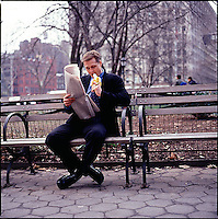 Man in suit sitting on park bench holding the newspaper and eating a banana<br />