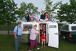 A group of people crammed inside and sitting on top of a Boler travel trailer.