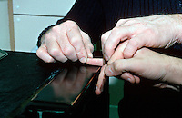 A police officer holding a suspects hand to ensure that the fingerprinting is performed in the correct way. This image may only be used to portray the subject in a positive manner..©shoutpictures.com..john@shoutpictures.com