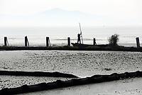 A man boats across Lake Tai, on the border of Zhejiang and Jiangsu Province in eastern China.