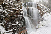 Avalanche Falls on Flume Brook in Lincoln, New Hampshire USA during a snow storm. This waterfall is located in Franconia Notch State Park in the Flume Gorge. Blowing snow can be seen in the image.