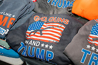 "A vendor displays pro-Trump hats, shirts, and other paraphernalia for sale as alt-right organization Super Happy Fun America demonstrates against facemasks, vaccines, and pandemic closures, and in support of the reelection of President Donald J. Trump near the residence of Massachusetts governor Charlie Baker in Swampscott, Massachusetts, on Sat., Sept. 26, 2020. Super Happy Fun America is most well known for organizing the Straight Pride Parade in Boston on August 31, 2019. Slogans and images on the shirts include ""God, Guns, and Trump"" and an image of Trump performing the fad dance move dabbing."