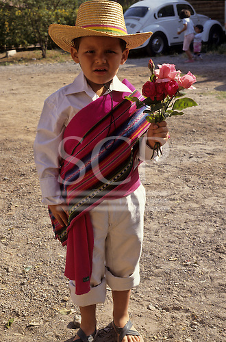 Santiago, Chile. Boy in traditional dress holding flowers.