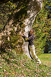 Germany, Bavaria, Upper Bavaria, Werdenfelser Land, Kruen: autumn scenery at lake Barmsee, woman embracing the trunk of an old maple tree | Deutschland, Bayern, Oberbayern, Werdenfelser Land, Kruen: Herbststimmung am Barmsee, Frau umarmt einen alten Ahornbaum