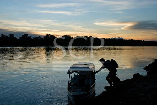 Xingu Indigenous Park, Mato Grosso State, Brazil. Aldeia  Capivara (Kaiabi). Patrick Cunningham boarding the boat at sunset.