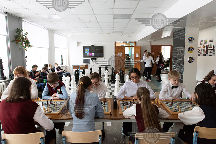 School children are playing chess during a break between lessons.
