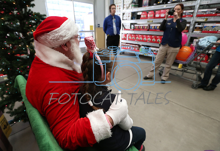 Students get their photo with Santa at the 10th annual Holiday with a Hero event at Walmart in Carson City, Nev., on Wednesday, Dec. 17, 2014. The event pairs 200 of Carson City's K-5th grade homeless students with a local heroes for Christmas shopping. <br />