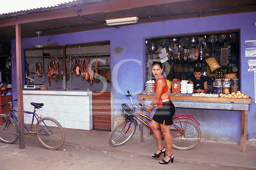 Altamira, Para State, Brazil. Woman in front of a convenience store with a bicycle; ham, eggs etc.
