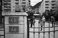 Switzerland. Canton Ticino. Viganello. A group of women and a man stand in a park and talk together. They all wear a mask on their faces to protect themselves from the Coronavirus (also called Covid-19). They all keep a social distance of 2 meters as a health security measure. A metal gate and a fence. Houses numbers on the wall. Viganello is a quarter of the city of Lugano. 23.12.2020  © 2020 Didier Ruef