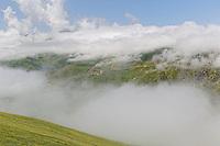 On the Anzer plateau, the clouds over the pasture lands let a village and its mosque peep through. ///Sur le plateau d'Anzer, les nuages sur les pâturages laissent deviner un village et sa mosquée.