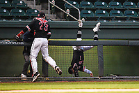 Third baseman Jared Williams (1) of the North Greenville Crusaders flips over the dugout railing in an unsuccessful attempt at a pop foul in the sixth inning of a game against the Queens University Royals on Tuesday, March 12, 2019, at Fluor Field at the West End in Greenville, South Carolina. Williams remained in the game. North Greenville won, 14-3. (Tom Priddy/Four Seam Images)
