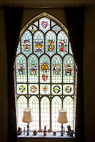 Detail of a large stained glass window with colourful coats of arms integrated into its panes