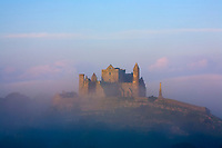 Ireland, Tipperary, Cashel, Summer, The sun breaks through the morning mist over the Rock of Cashel, The Rock of Cashel was a castle and seat of the ancient Eoghnacht Chiefs of Munsteran, and is now an important historic site and one of Ireland's most popular tourist sites