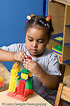 Education Preschool 3-4 year olds manipulatives girl making construction from colorful plastic bricks vertical