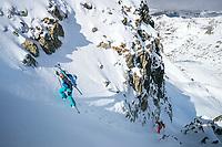 A ski tour through the Pirin Mountains of Bulgaria. A skier carries their skis on the Kamenitsa Mountain from the Tevno Ezero Hut.