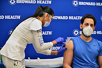 FORT LAUDERDALE, FLORIDA - DECEMBER 23: Leonida Lipshy, RN in the COVID unit at the Broward Health Medical Center, gives Dr. Nadav Fields, DO., internal medicine a shot of the Moderna COVID-19 vaccine at Broward Health Imperial Point on December 23, 2020 in Fort Lauderdale, Florida. Broward Health Medical Center began vaccinating frontline healthcare workers last week with the Pfizer-BioNtech COVID-19 vaccine and are continuing to inoculate frontline caregivers with both of the vaccines after the arrival of the Moderna.  <br /> CAP/MPI10<br /> ©MPI010/Capital Pictures