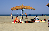 Banjul, Gambia. Tourists on the beach with sunbeds and thatched sunshades.