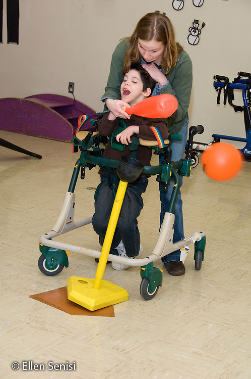 MR / Albany, NY.Langan School at Center for Disability Services .Ungraded private school which serves individuals with multiple disabilities.Teacher's aide assists child in a gait trainer with hitting the ball during a modified game T-ball during Adaptive Physical Education class (APE). Boy: 8, cerebral palsy, spastic quadriplegic, nonverbal with expressive and receptive language delays.MR:Neu1;Hac2.© Ellen B. Senisi