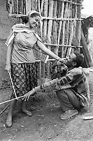Ethiopia. West Gujam. Danbecha district. Anjeni is a small village. A kneeled man flirts with a young woman, wearing a t-shirt from Samur beach with the design of palm trees. The walls of the house are made of with wood sticks and mud. © 1996 Didier Ruef
