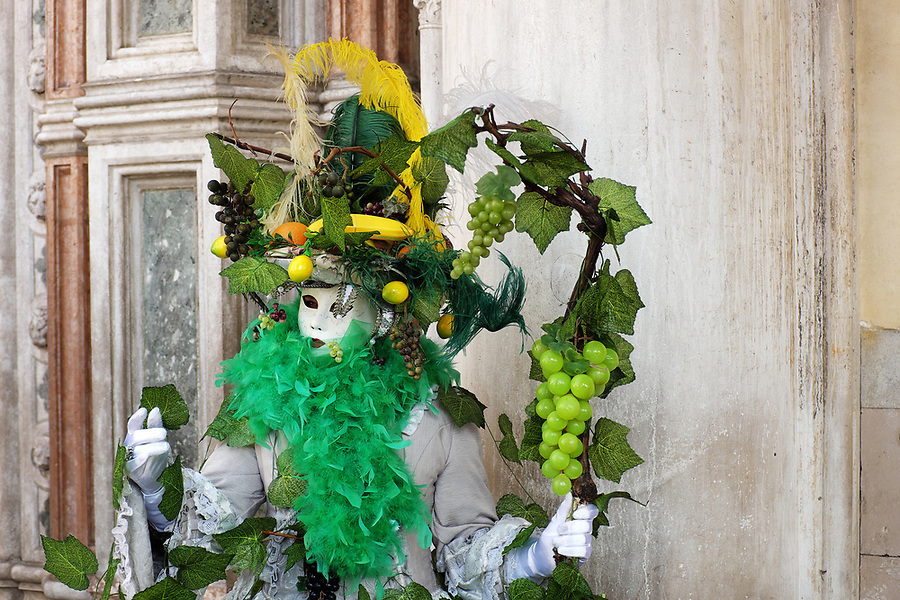 Woman dressed in traditional mask and fruit costume for Venice Carnival standing at Doge's Palace, Piazza San Marco, Venice, Veneto, Italy