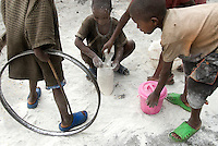 In the Mugunga I IDP (Internally Displaced Persons) camp, children clean flour off the ground after food distribution.