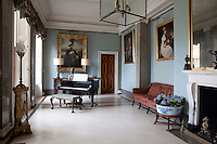 In the pale blue music room, a grand piano stands on a smooth marble floor
