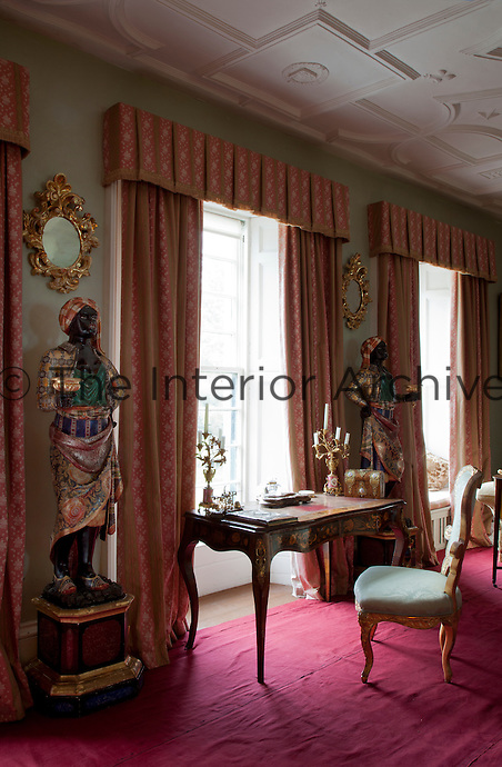 Two antique black amores flank one of the drawing room windows