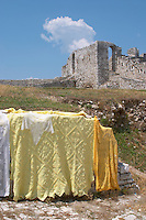Part of the city wall and traditional embroidered cloth and shawls for sale. Berat upper citadel old walled city. Albania, Balkan, Europe.