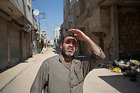 A man looks up as a Syrian Airforce fighter jet circles over a nearby Free Syrian Army (FSA) command centre in Aleppo. The command center was bombed the following day killing nearby civilians in a bakery.