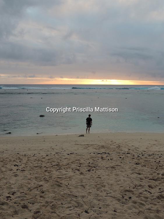 Rarotonga, Cook Islands - September 20, 2012:  A man watches the sunset over the lagoon.