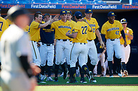 Michigan Wolverines relief pitcher William Tribucher (22) high fives teammates, including Benjamin Keizer (14) Tommy Henry (47), and Jayce Vancena (20) during a game against Army West Point on February 17, 2018 at Tradition Field in St. Lucie, Florida.  Army defeated Michigan 4-3.  (Mike Janes/Four Seam Images)