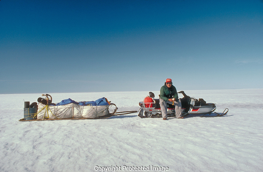 Snowmobiler takes a break on the spring ice of Great Slave Lake