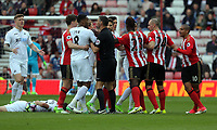SUNDERLAND, ENGLAND - MAY 13: Referee Andre Marriner (C) tries to calm down a melee between players after Gylfi Sigurdsson of Swansea City (L) was fouled by Wahbi Khazri of Sunderland (R) during the Premier League match between Sunderland and Swansea City at the Stadium of Light, Sunderland, England, UK. Saturday 13 May 2017